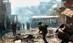 """A handout picture released by the official Syrian Arab News Agency (SANA) on July 25, 2012, shows forces loyal to President Bashar al-Assad fighting in the al-Qadam district of  Damascus. The Syrian army and rebels on July 25, sent reinforcements to Aleppo to join the intensifying battle for the country's second city, as UN chief Ban Ki-moon urged the world """"to stop the slaughter."""" AFP"""